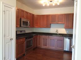 Maple Creek Kitchen Cabinets by American Woodmark Delray Maple Cognac With Tan And Brown Granite