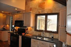 beige tile backsplash and black grenite countertops connected by