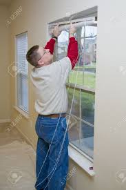 repair man replacing window blinds in apartment making ready