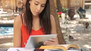 Student Doing Homework With Help Of Tablet Computer In Cafe Stock     Shutterstock