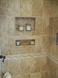 a ceramic tile shower with 2 inset shelves in a bathroom in