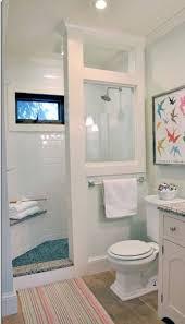 bathroom towel rack and wall mirror plus glass window and tile