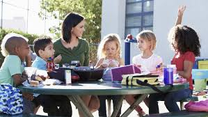 Afterschool Programs and Homework Help  What to Look For Teacher and a group of children sitting at a table outside having snacks   Benefits of