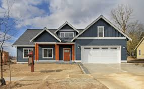 blue siding craftsman style home with wood posts and front door