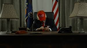 trump desk trump wide shot of sitting at desk tweeting on his phone stock