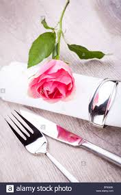 romantic formal elegant table setting with a single pink rose and