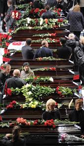 People pass by coffins during a memorial ceremony for victims from the Russian ice hockey team