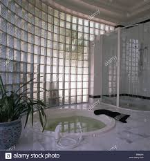 curved glass brick wall in modern bathroom with sunken jacuzzi curved glass brick wall in modern bathroom with sunken jacuzzi bath and glass shower unit