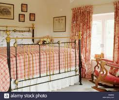 red checked bedlinen on antique brass bed in country bedroom with