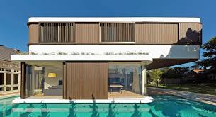 a modern house with a wraparound swimming pool design milk