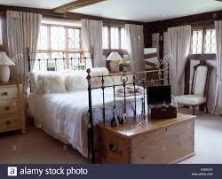 fluffy white cushions and white linen on antique brass bed in