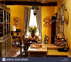 large painted dresser in bright yellow french country kitchen