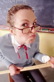 female teacher with glasses holding a ruler