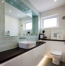 glass rectangular tiles frame a large recessed mirror reflecting