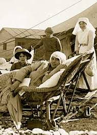 Sick nursing sisters  with eiderdowns and blankets lie outside on beds  Wooden buildings and Gallipoli and the Anzacs