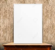 empty white frame on wooden table at wood wall in background mock