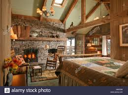 wooden bed facing stone fireplace with lit fire in country style