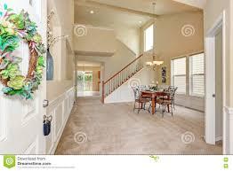 opened front door to high ceiling beige dining room interior