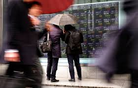 Asian shares tumble on jitters over Trump reform agenda   Tucson      AP Photo Shizuo Kambayashi   Men look at an electronic stock indicator of