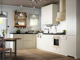 an off white country kitchen with black worktops combined with
