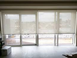 sunscreen roller blinds over bi fold doors in living room