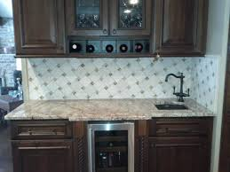 glass subway tile backsplash with white cabinets and grey