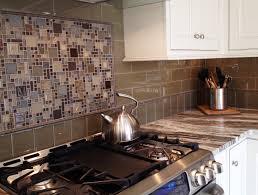 glass tile backsplash with framed mosaic tile insert over the