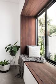 the contemporary renovation of a 100 year old home in australia this modern bedroom has a wood framed window seat that overlooks the garden