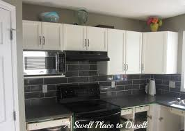 brown cabinetry with mosaic ceramic backsplashes tile iwth granite