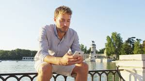 Man sms texting using app on smart phone at sunset in city park  Handsome young