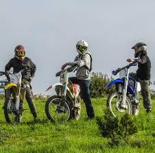 motocross dirt bikes three men riding on motocross dirt bikes under grey sky during