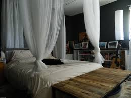 classy black stained wooden king bed with white canopy curtain