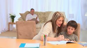 Parents Helping Their Children With Their Homework At A Desk Stock