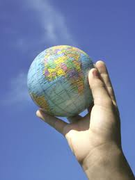 Image of a child's hand holding the world