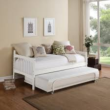 short white wooden daybed with orange pillow and mattress