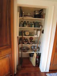 rectangle white pantry cabinet with five rows shelf on white wall