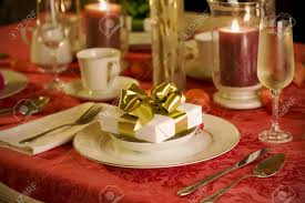elegant christmas table setting in red with gold gift as focal