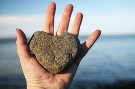 hand holding heart shaped rock