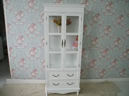 tall white bookshelf with double cabinet door on the bottom