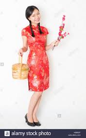 young asian woman in traditional cheongsam dress holding gift